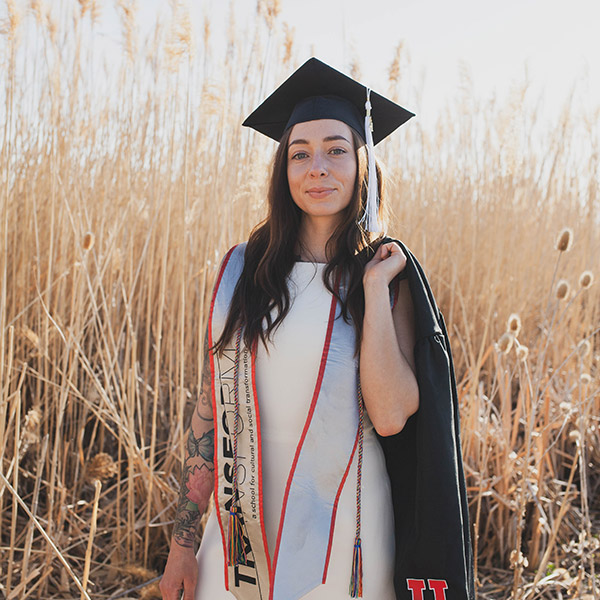Brandy poses in her graduation regalia in a golden field of tall grass