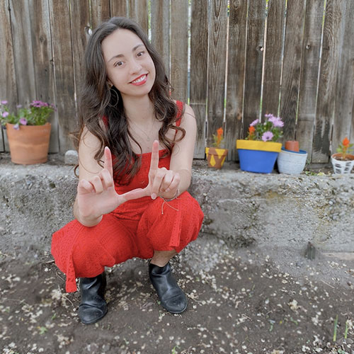 Kadelyn Egan poses by a fence and potted plants.